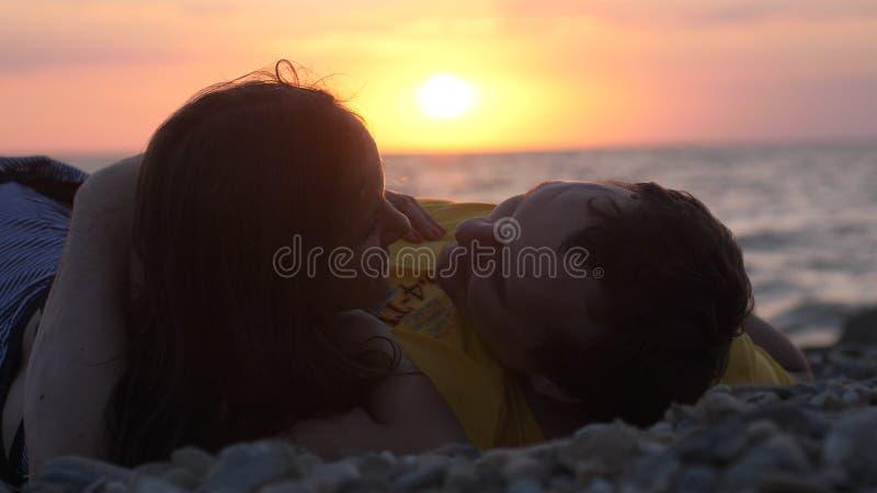 Koppla ihop förälskat lägger romantiskt under solen ser sig tillsammans under härlig solnedgång royaltyfri fotografi