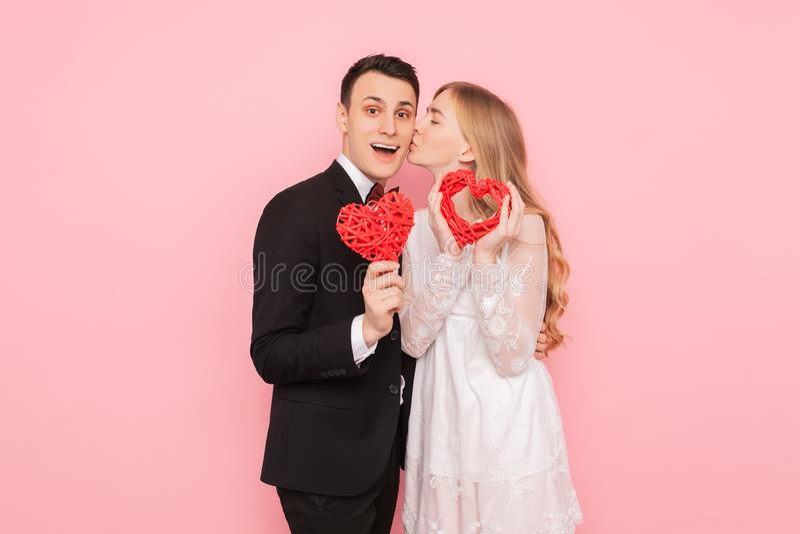 Koppla ihop förälskat, mannen och kvinnan som rymmer röda hjärtor, på rosa bakgrund, vändagbegreppet arkivbilder