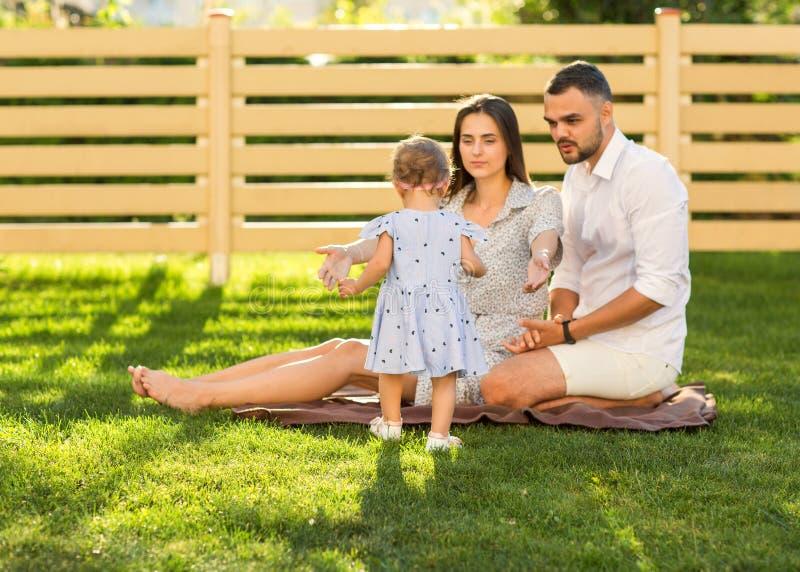 Koppla ihop förälskat med den lilla dottern på en picknick nära deras hem, royaltyfri foto