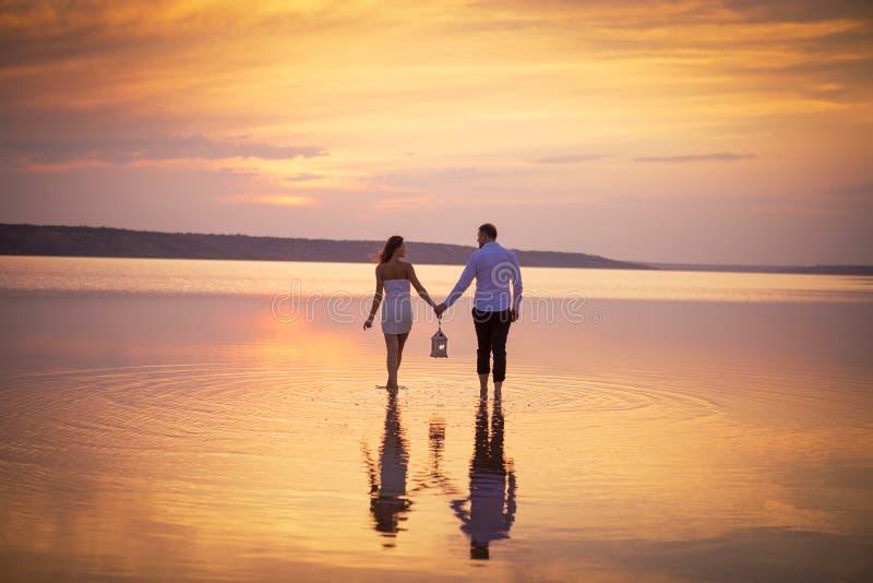 Koppla ihop förälskat på den orange solnedgången för sjön som wailking i vatten royaltyfri foto