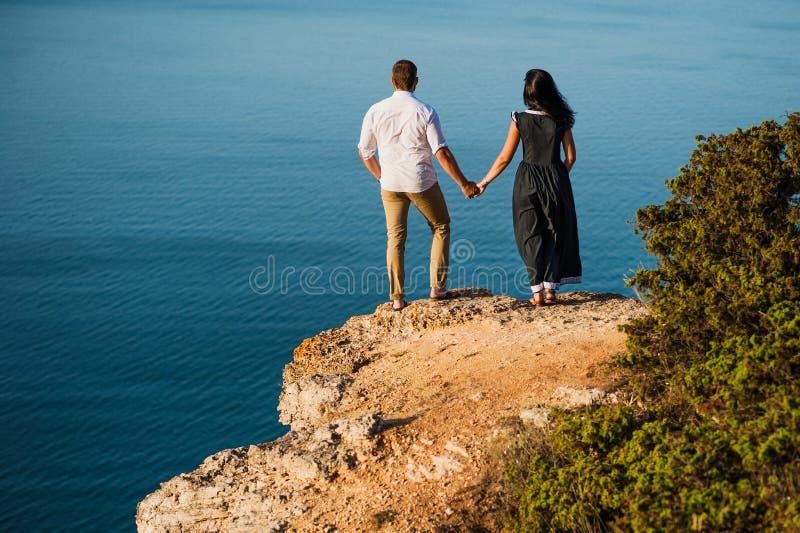 Koppla ihop förälskat på gryning vid havet Br?llopsresatur l?pande kvinna f?r man Lyckliga par vid havssikten från baksidan man o arkivfoton