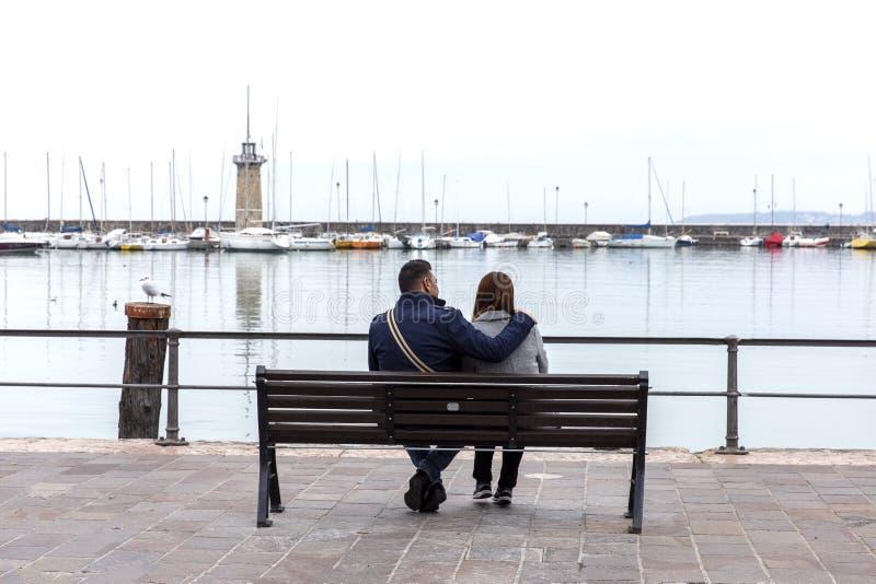Koppla ihop förälskat på kusterna av sjön Garda, Desenzano di Garda, Italien Förälskade par på stranden Par som kramar på en bänk royaltyfri foto