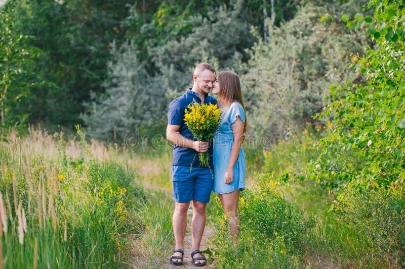 Koppla ihop förälskat på naturen med en bukett av lösa gula blommor royaltyfri foto
