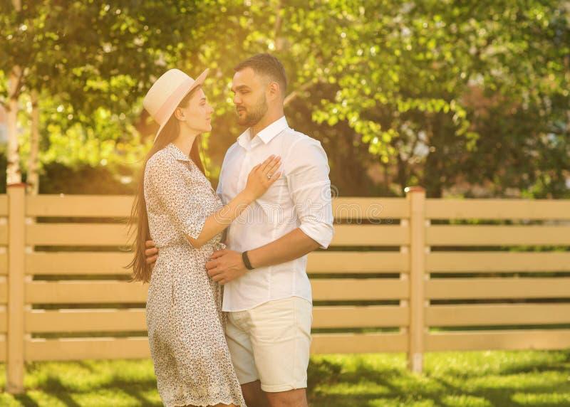 Koppla ihop förälskat på solnedgången som går i den lyckliga parkera, amerikansk dre royaltyfria bilder