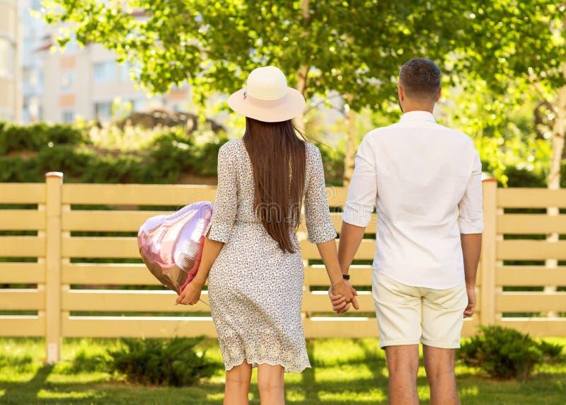 Koppla ihop förälskat på solnedgången som går i den lyckliga parkera, amerikansk dre royaltyfri bild