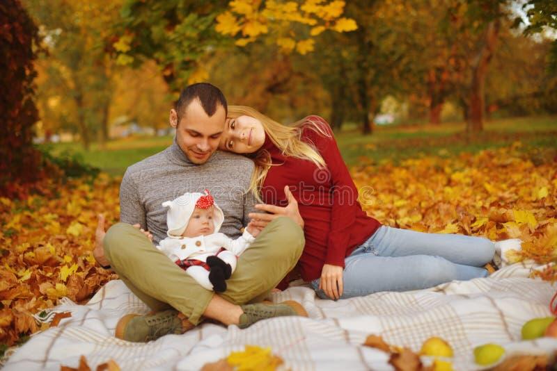 Koppla ihop förälskat sammanträde på höst som stupade sidor i parkerar, sitt på filten som tycker om en härlig höstdag Lyckligt fotografering för bildbyråer