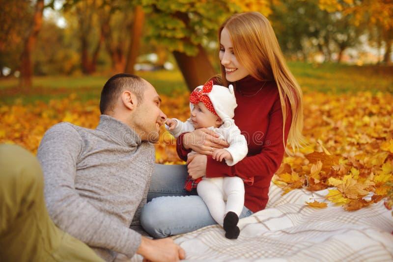 Koppla ihop förälskat sammanträde på höst som stupade sidor i parkerar, sitt på filten som tycker om en härlig höstdag Lyckligt royaltyfri foto