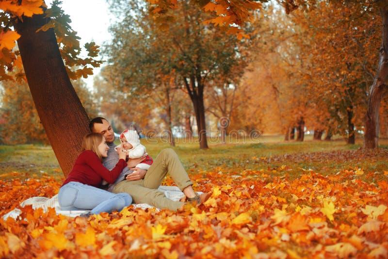 Koppla ihop förälskat sammanträde på höst som stupade sidor i parkerar, sitt på filten som tycker om en härlig höstdag Lyckligt royaltyfri bild