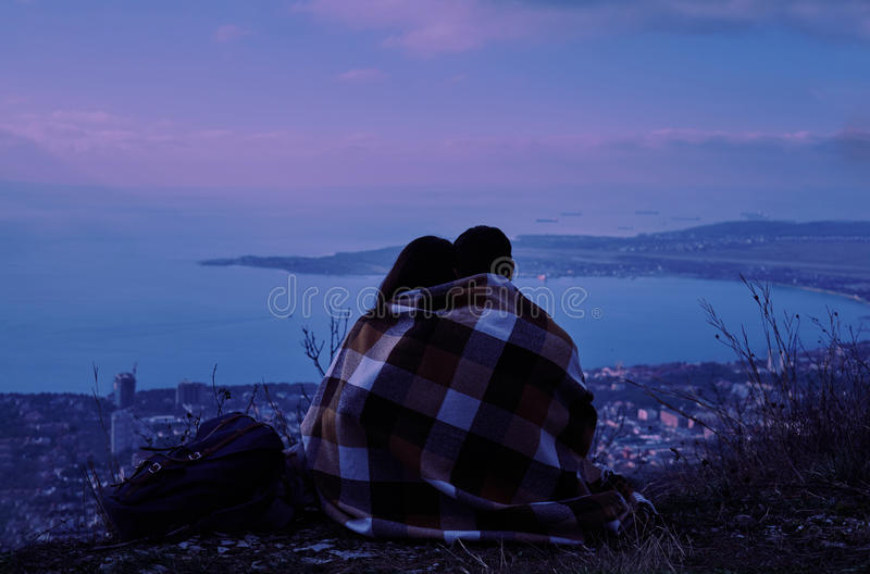 Koppla ihop förälskat sammanträde på kullen ovanför staden i natt arkivfoton