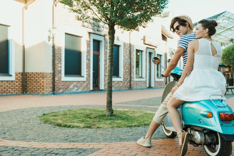 Koppla ihop förälskat sammanträde på sparkcykeln på stadsgatan royaltyfri foto