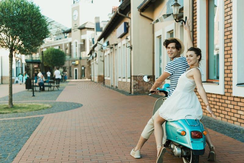 Koppla ihop förälskat sammanträde på sparkcykeln på stadsgatan royaltyfria foton