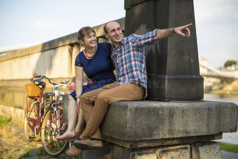 Koppla ihop förälskat sammanträde på trottoarkantinvallningen och samtal passionately royaltyfri foto