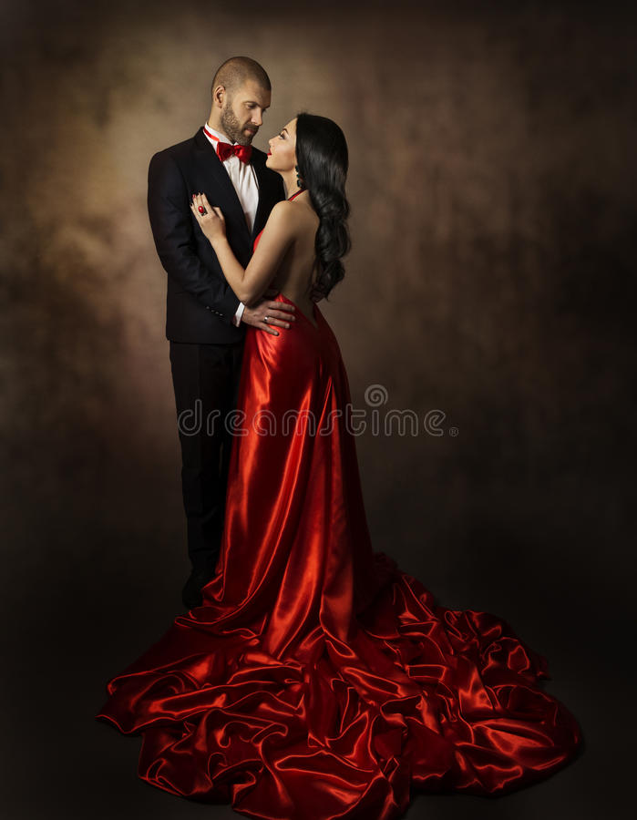 Koppla ihop förälskat, vänner kvinna och man, den klassiska dräkten för glamour och klänningen med den långa svansen, modeskönhet fotografering för bildbyråer