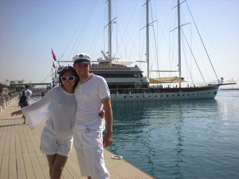 Koppla ihop f?r?lskat p? bakgrunden av havet och yachten Resa p? yachten av ett ungt par royaltyfria bilder