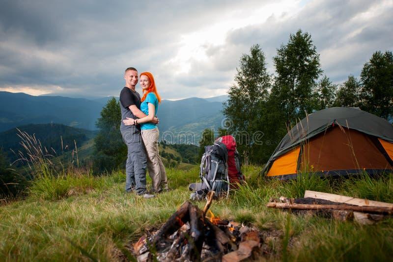 Koppla ihop fotvandrare som står nära lägerelden, tältet, ryggsäckar arkivbild