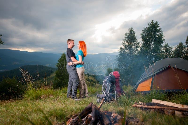 Koppla ihop fotvandrare som står nära lägerelden, tältet, ryggsäckar arkivfoto