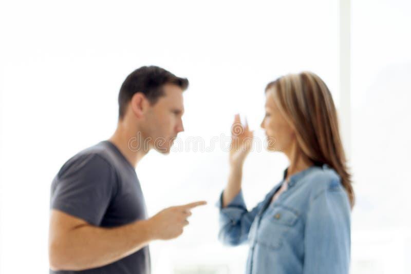 Koppla ihop frågor - mannen och kvinnan som argumenterar om personliga problem i deras förhållande - som är suddiga på avsikt royaltyfria bilder