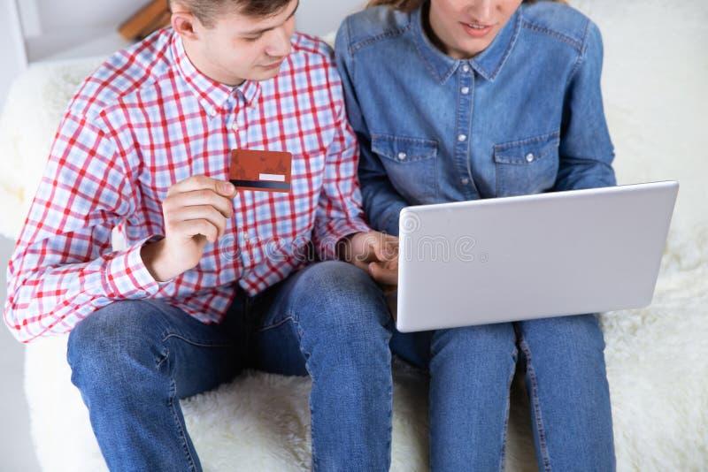 Koppla ihop framställning av att shoppa online-sammanträde hemma på soffan och av att använda kreditkorten arkivfoto