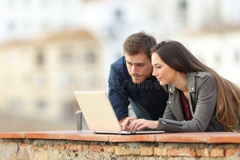Koppla ihop genom att använda en bärbar dator i en terrass på ferie royaltyfri bild