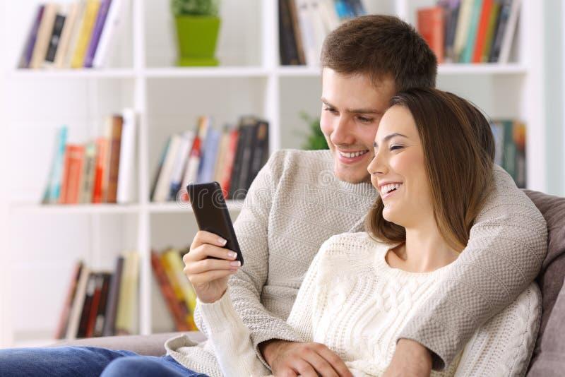 Koppla ihop hållande ögonen på massmedia på en smart telefon som hemma sitter fotografering för bildbyråer
