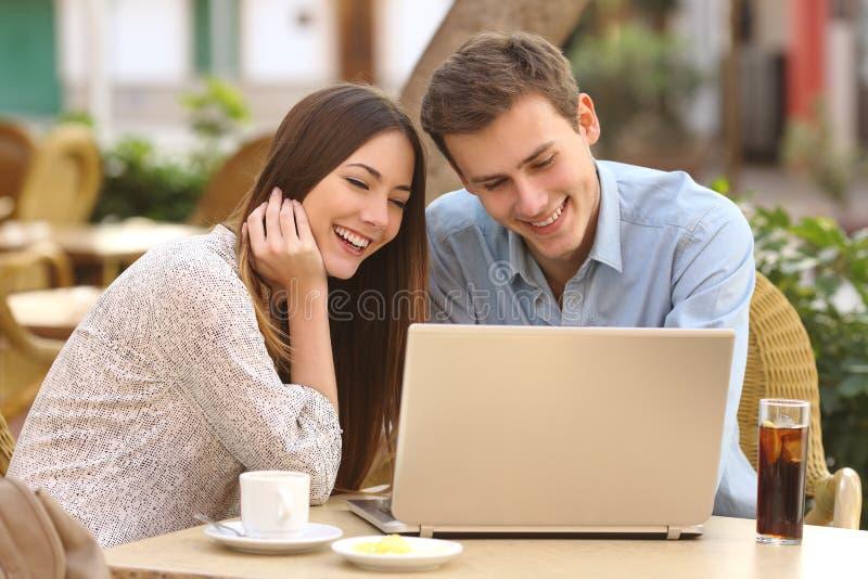 Koppla ihop hållande ögonen på massmedia i en bärbar dator i en restaurang royaltyfria foton