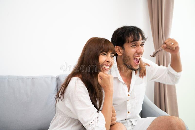 Koppla ihop hållande ögonen på tv och att sitta på en soffa royaltyfria bilder