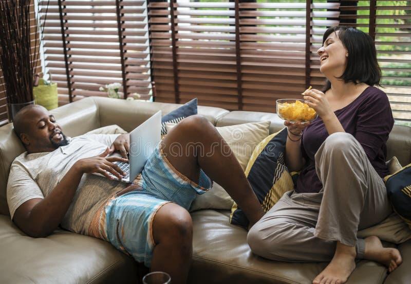 Koppla ihop hållande ögonen på tv på soffan och användabärbara datorn royaltyfria foton
