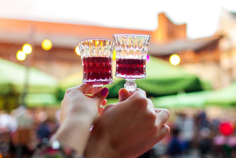 Koppla ihop hållande exponeringsglas med rött vin i utomhus- restaurang Man- och kvinnarostat bröd i kafé arkivbilder