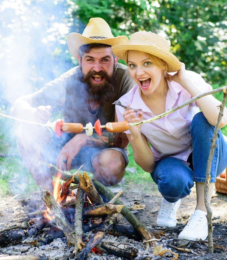 Koppla ihop hungriga turister som grillar korvar på pinnenaturbakgrund Korv för skog för par förälskad campa stekhet på royaltyfri bild