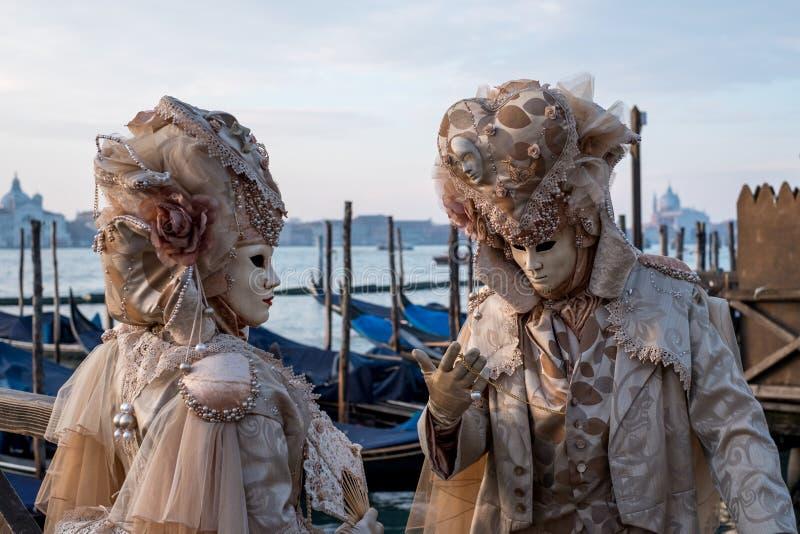 Koppla ihop i dräkten och maskeringar som står med tillbaka till Grand Canal, San Giorgio i bakgrunden, under den Venedig karneva royaltyfria foton
