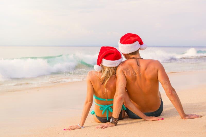 Koppla ihop i jultomtenhattar som sitter på stranden royaltyfri foto