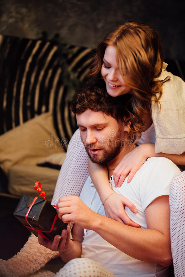Koppla ihop in i pyjamas som vilar på golvet bredvid sängen och, ge sig gåvor i askar fotografering för bildbyråer