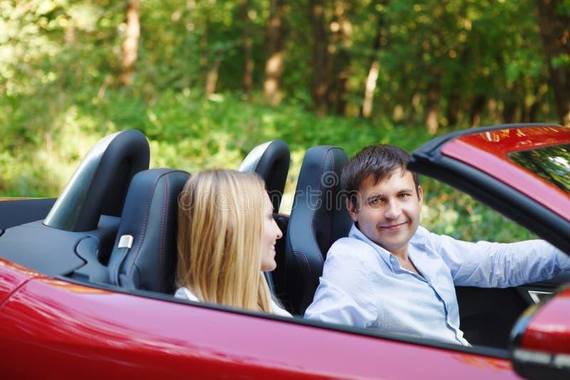 Koppla ihop i röd cabriolet i en solig dag royaltyfria bilder