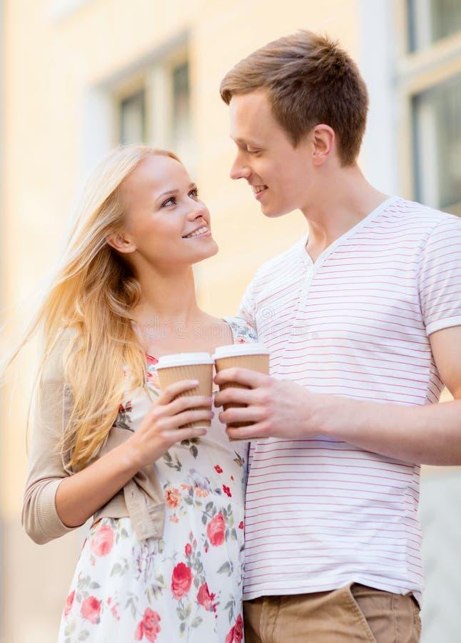 Koppla ihop i staden med takeaway kaffekoppar arkivfoton