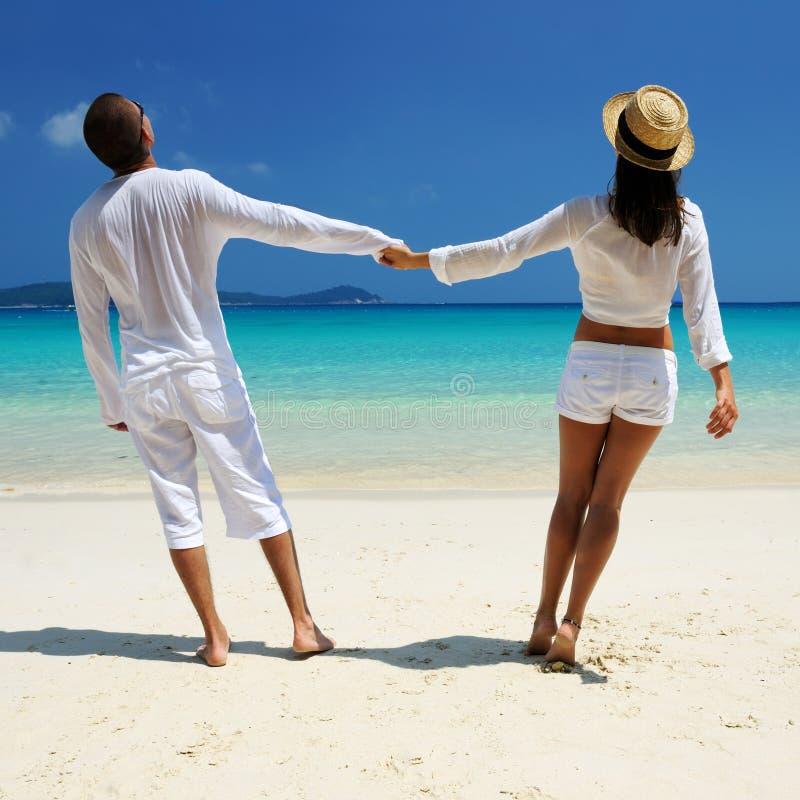 Koppla ihop i vit på en strand arkivfoton