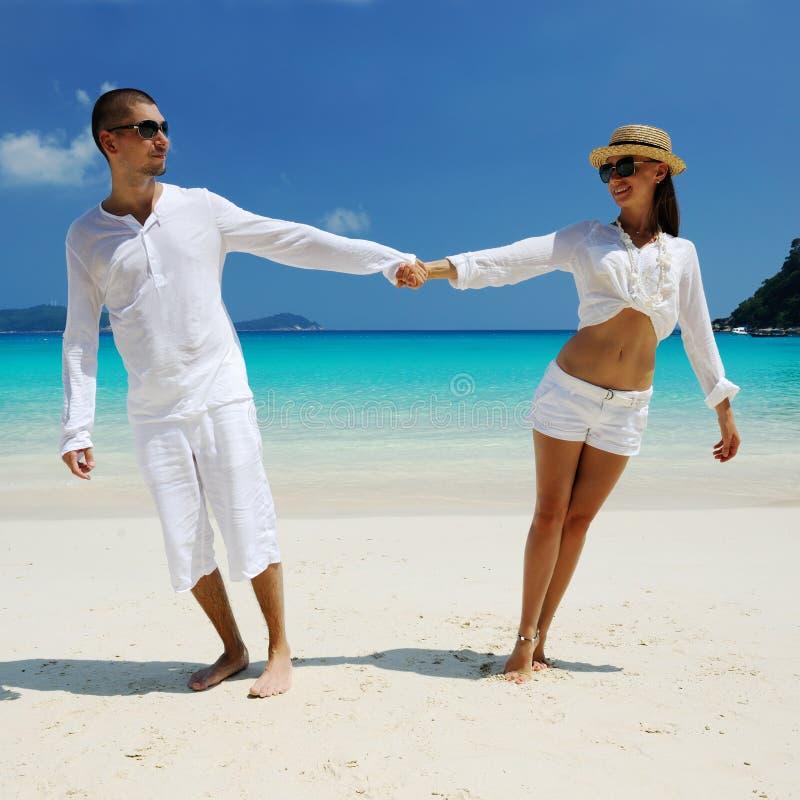 Koppla ihop i vit på en strand royaltyfri fotografi
