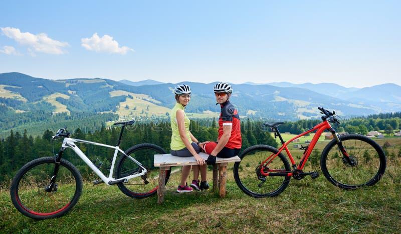 Koppla ihop idrottsmancyklister som nära sitter på cyklar för träbänken som ser till kameran fotografering för bildbyråer