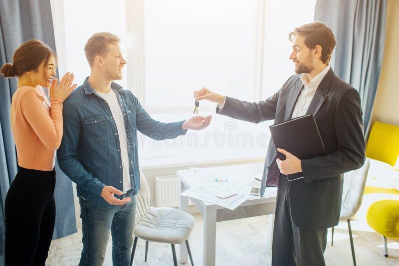 Koppla ihop köp- eller hyralägenheten tillsammans Fastighetsmäklaren ger tangenter till den unga mannen Lyckligt tycka om för kvi arkivbilder