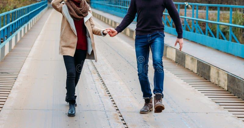 Koppla ihop körningar och hopp på bron som rymmer händer, nära vattnet, hösten förälskelse och familjen, ett datum i parkerar vid fotografering för bildbyråer