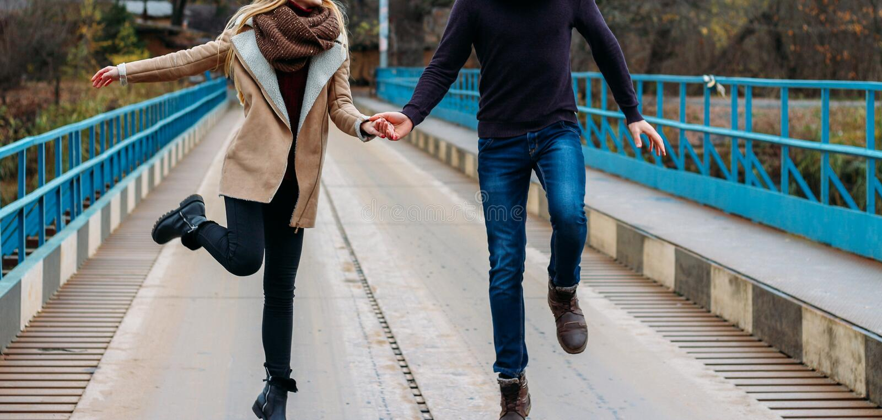 Koppla ihop körningar och hopp på bron som rymmer händer, nära vattnet, hösten förälskelse och familjen, ett datum i parkerar vid arkivfoto