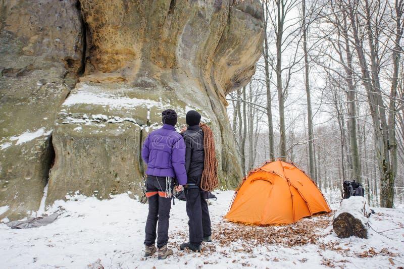 Koppla ihop klättrare i en vintertid nära campa för berg arkivfoton
