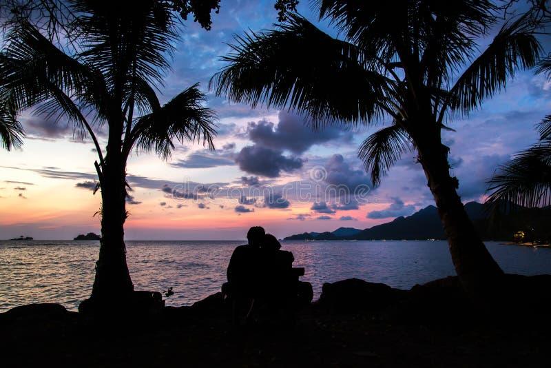 Koppla ihop konturkeln och den hållande ögonen på solen på solnedgången på beaen royaltyfri fotografi