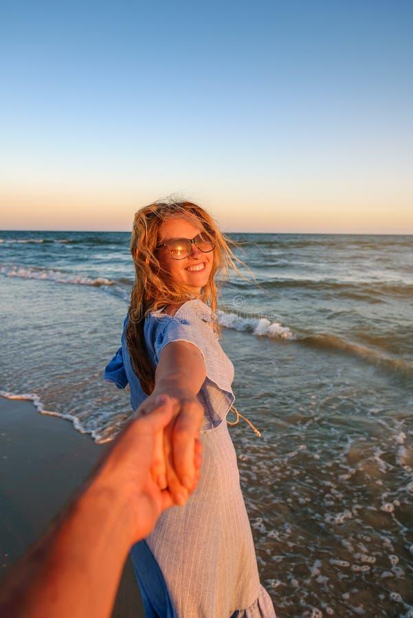 Koppla ihop loppet för sommarsemestern - kvinnan som går på den romantiska bröllopsresastranden, semestrar rymma handen av pojkvä arkivfoto