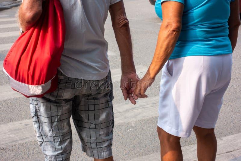 Koppla ihop man- och kvinnainnehavhänder som går på gatan arkivfoton