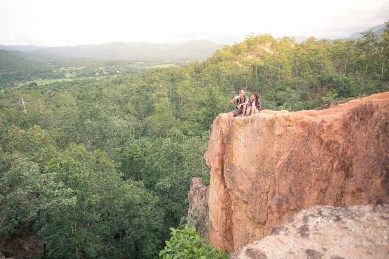 Koppla ihop man- och kvinnasammanträde på klippan som tycker om berg och clo arkivfoton