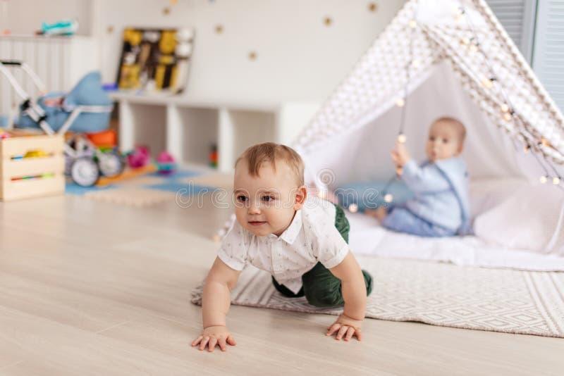 Koppla ihop manliga små barn som tycker om rörelse och enkla lekar i mysig solig barnkammare fotografering för bildbyråer