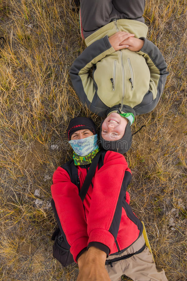 Koppla ihop mannen och kvinnan som gör selfieturister som ligger på gräset royaltyfri foto