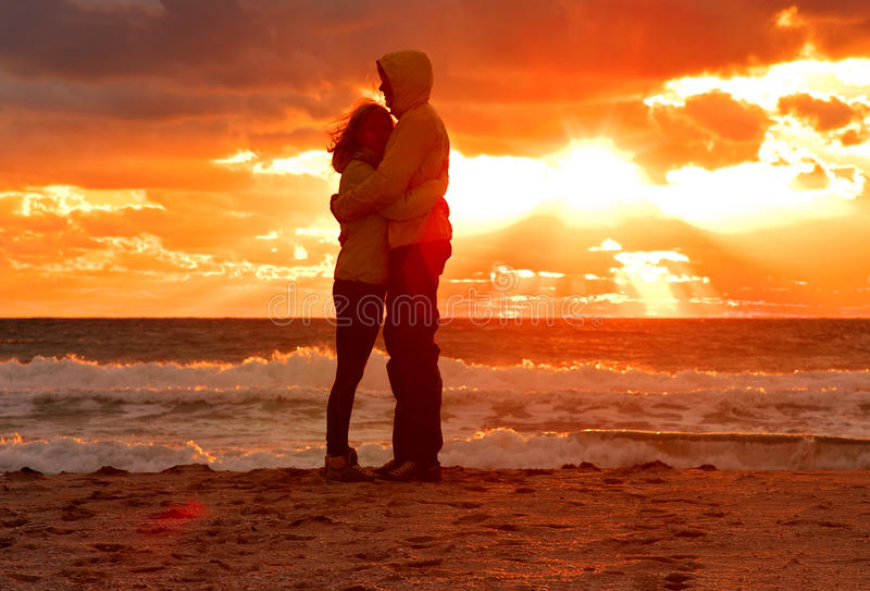 Koppla ihop mannen och kvinnan som kramar förälskat bli på strandsjösidan med solnedgånglandskap royaltyfri bild