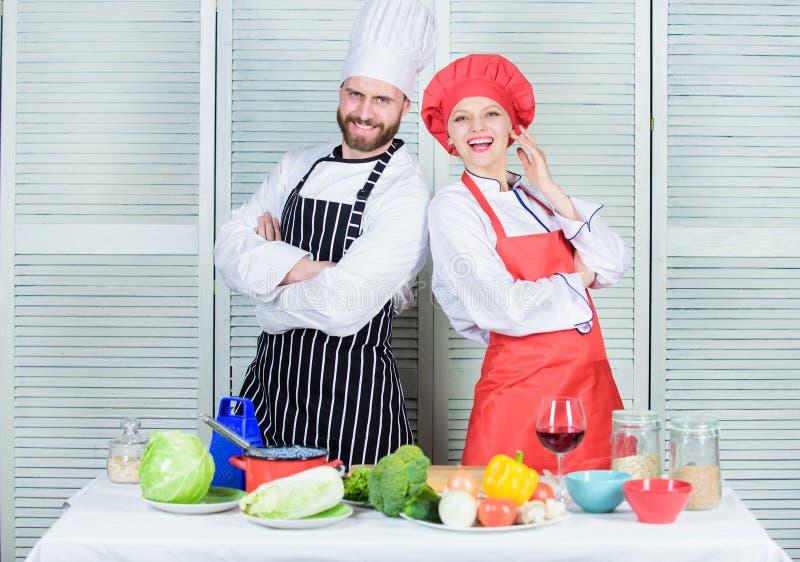 Koppla ihop matlagningmatst?llen Kulinariska partners f?r kvinna och f?r sk?ggig man L?cker familjmatst?lle Laga mat för anlednin arkivfoto