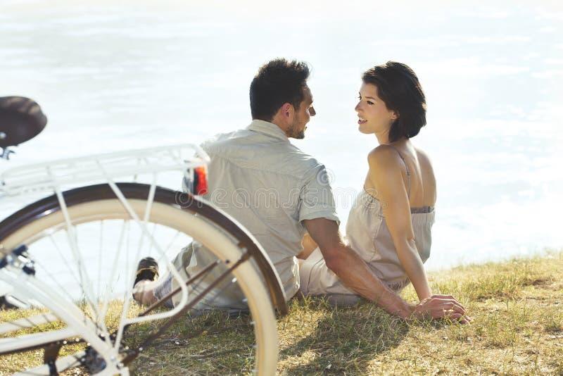 Koppla ihop med cykeln som framme vilar av sjön royaltyfria foton